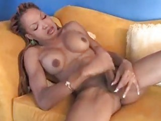 Muscular ebony shemale plays with her giant tool and cums